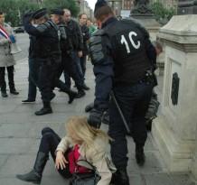 Les CRS saisissent au cou une opposante, avant de la jeter au violemment contre un trottoir